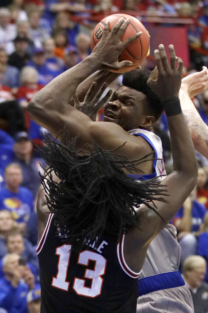 Kansas center Udoka Azubuike, back, rebounds over Oklahoma State guard Isaac Likekele (13) during the first half of an NCAA college basketball game in Lawrence, Kan., Monday, Feb. 24, 2020. (AP Photo/Orlin Wagner)