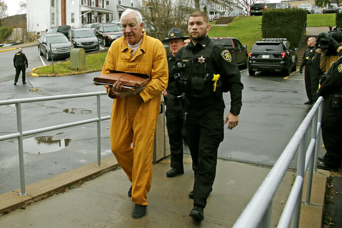 Former Penn State University assistant football coach Jerry Sandusky, left, arrives at the Centre County Courthouse for resentencing on his conviction of 45 counts of child sexual abuse Friday, Nov. 22, 2019, in Bellefonte, Pa. Sandusky was convicted in 2012 and sentenced to 30 to 60 years.  (AP Photo/Gene J. Puskar)