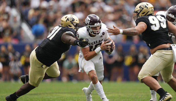 Texas A&M quarterback Zach Calzada, center, is stopped after a short gain by Colorado defensive linemen Na'im Rodman, left, and Jalen Sami in the second half of an NCAA college football game Saturday, Sept. 11, 2021, in Denver. Texas A&M won 10-7. (AP Photo/David Zalubowski)