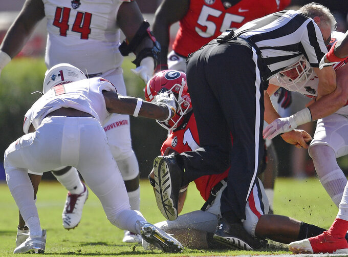 Austin Peay defensive back Malik Davis (1) tackles Georgia quarterback Justin Fields (1) as Austin Peay tight end Jack McDonald (38) collides with the umpire during the first half of an NCAA college football game, Saturday, Sept. 1, 2018, in Athens, Ga. (AP Photo/Mike Stewart)