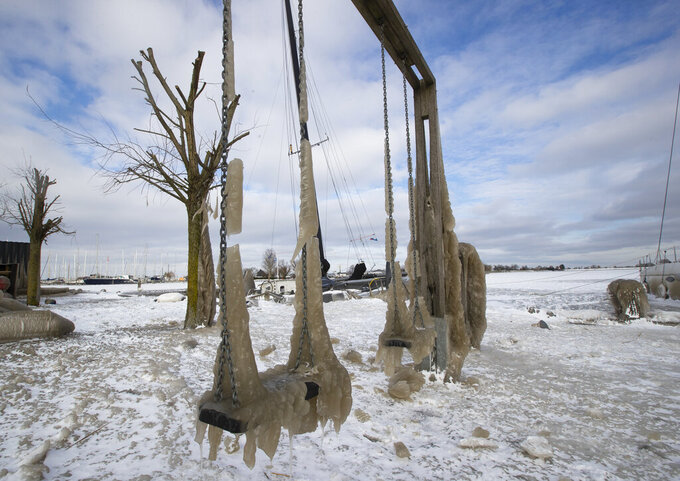 Swings froze after strong winds swept waves ashore in the marina of Monnickendam, Netherlands, Tuesday, Feb. 9, 2021. With freezing temperatures forecast for more than a week in the Netherlands, ice fever is sweeping the nation, offering a welcome respite from grim coronavirus news while also creating a challenge for authorities trying to uphold social distancing measures. (AP Photo/Peter Dejong)
