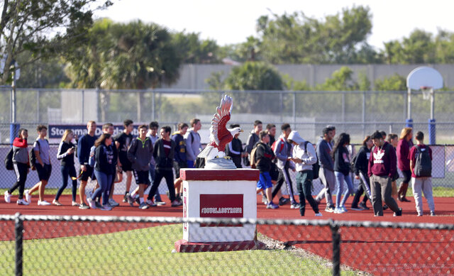 FILE - In this March 14, 2018 file photo, Students from Marjory Stoneman Douglas High School walkout to the football field for 17 minutes of silence in honor of the 17 victims killed at the school.  The Florida Supreme Court is blocking an assault weapons ban from going to voters in 2022, saying in a Thursday, June 4 2020 ruling that the ballot summary is deceptive because it doesn't clearly state that a grandfathering clause applies to the owner, not the gun itself.(Mike Stocker/South Florida Sun-Sentinel via AP, File)