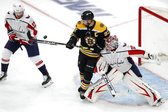 Boston Bruins' Patrice Bergeron (37) battles Washington Capitals' Evgeny Kuznetsov (92) and Ilya Samsonov (30) for control of the puck during the first period in Game 4 of an NHL hockey Stanley Cup first-round playoff series, Friday, May 21, 2021, in Boston. (AP Photo/Michael Dwyer)