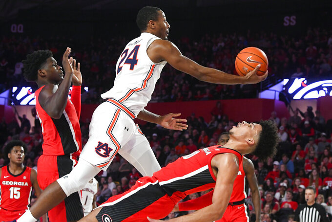 Auburn forward Anfernee McLemore (24) goes up for a shot as Georgia forward Toumani Camara (10) tries to draw a charge during the first half of an NCAA college basketball game Wednesday, Feb. 19, 2020, in Athens, Ga. (AP Photo/John Amis)