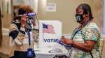 Workers prepare at a polling station, Tuesday, Aug. 11, 2020, in Atlanta. Voters in Georgia return to the polls Tuesday for runoffs to settle party nominations in four congressional races and 17 legislative races, as well as a closely watched contest for who will claim the Democratic nod for district attorney in Fulton County. (John Spink/Atlanta Journal and Constitution via AP)