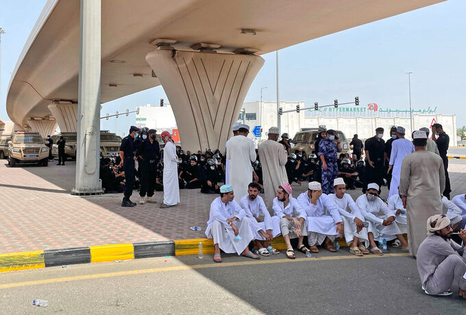 People and security forces talk under a bridge, in Sohar, Oman, Tuesday, May 25, 2021. On Tuesday, dozens of protesters angry over firings and the poor economy of Oman marched in Sohar, a city some 200 kilometers northwest of the capital, marking a third day of demonstrations in the typically subdued sultanate. (AP Photo)