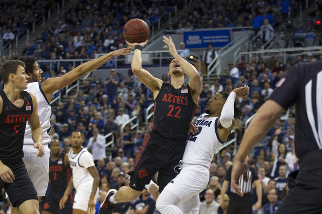 San Diego State guard Malachi Flynn (22)shoots over Nevada guard Jazz Johnson (22) during the first half of an NCAA college basketball game played at Lawlor Events Center in Reno, Nev., Saturday, Feb. 29, 2020. (AP Photo/Tom R. Smedes)