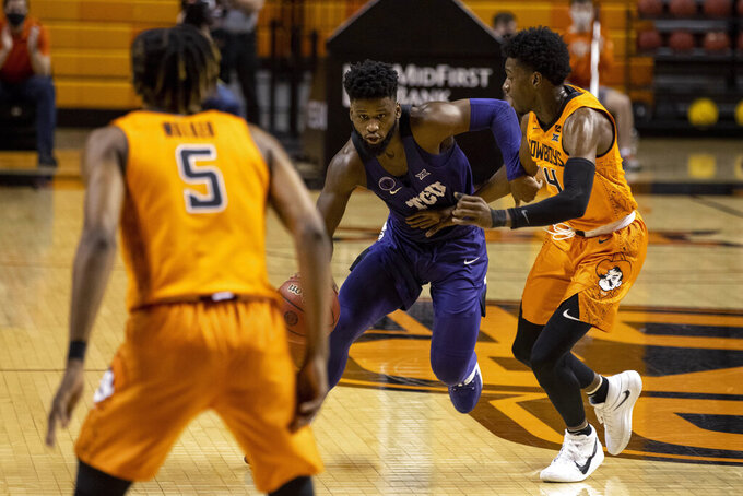 Oklahoma State's Bryce Williams (14) guards Texas Christian guard Mike Miles (1) during the first half of the NCAA college basketball game in Stillwater, Okla., Wednesday, Dec. 16, 2020. (AP Photo/Mitch Alcala)