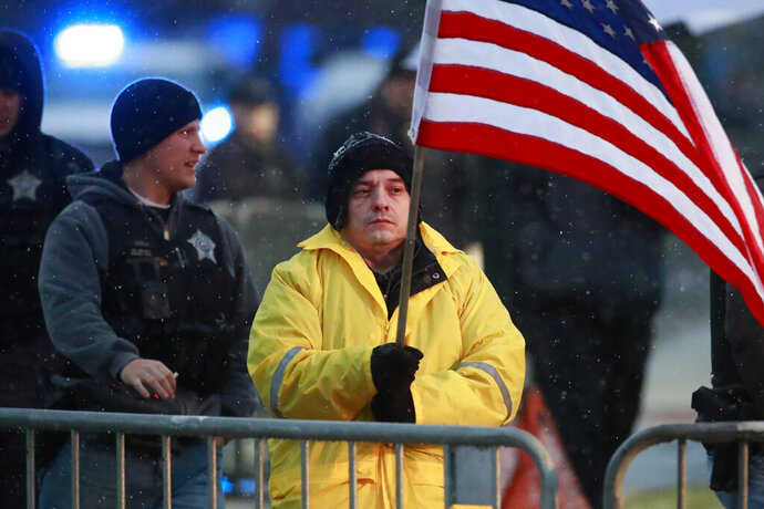 FILE - In this Nov. 25, 2018 file photo, State Rep. Jaime Andrade holds a flag outside the visitation for Chicago police Officer Samuel Jimenez at a funeral home in Des Plaines, Ill.A federal bribery charge against an Illinois legislator has led to questions about whether lawmakers be allowed to lobby other units of government. Illinois like most states allows legislators to lobby outside state government. Andrade said he registered as a Chicago lobbyist and started charging for his services when the state budget crisis from 2015 to 2017 forced lawmakers to go without paychecks. (Nuccio DiNuzzo/Chicago Tribune via AP File)