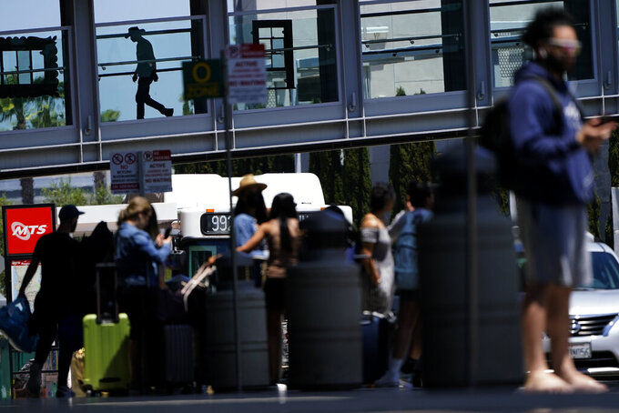 People arrive and depart from the airport ahead of Memorial Day weekend Friday, May 28, 2021, in San Diego. (AP Photo/Gregory Bull)