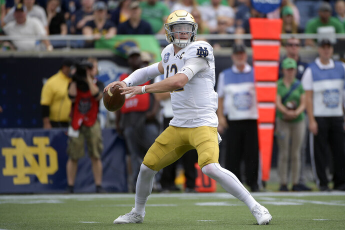 File-Notre Dame quarterback Ian Book (12) throws a pass during the first half of the Camping World Bowl NCAA college football game against Iowa State Saturday, Dec. 28, 2019, in Orlando, Fla. Head coach Brian Kelly has seen growth in the 6-foot, 208-pound Book since quarterbacks coach Tom Rees became the team's new offensive coordinator prior to the team's Camping World Bow victory over Iowa State. (AP Photo/Phelan M. Ebenhack, File)