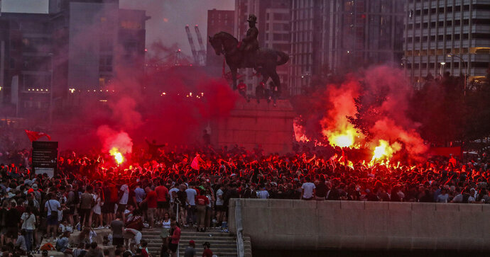 Liverpool soccer fans let off flares outside the Liver Building in Liverpool, England, Friday, June 26, 2020. Their team clinched the English Premier League title. Liverpool took the title after Manchester City failed to beat Chelsea on Wednesday evening. (Peter Byrne/PA via AP)