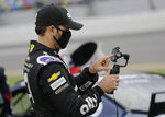 Jimmie Johnson uses his cell phone on pit road before the NASCAR Cup Series auto race at Daytona International Speedway, Saturday, Aug. 29, 2020, in Daytona Beach, Fla. Johnson was involved in a late-race crash. (AP Photo/Terry Renna)