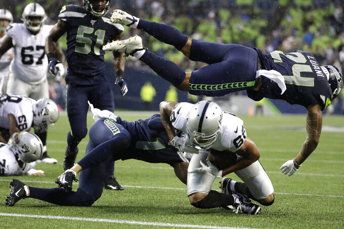 Seattle Seahawks defensive back Shalom Luani (24) flies over Oakland Raiders wide receiver Marcell Ateman (88) after Ateman made a catch during the first half of an NFL football preseason game Thursday, Aug. 29, 2019, in Seattle. (AP Photo/Elaine Thompson)