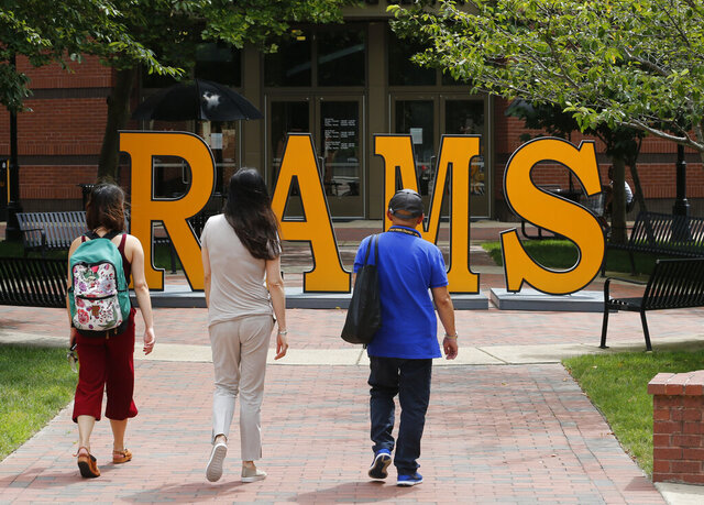 FILE - In this June 20, 2019, file photo students walk around a RAMS sign at Virginia Commonwealth University in Richmond, Va. Families with 529 college savings plans may have seen their totals tumble due to recent economic events caused by the coronavirus pandemic. But that downturn also has interest rates on undergraduate federal student loans potentially decreasing to less than 3%, the lowest rate in more than 15 years.  (AP Photo/Steve Helber, File)