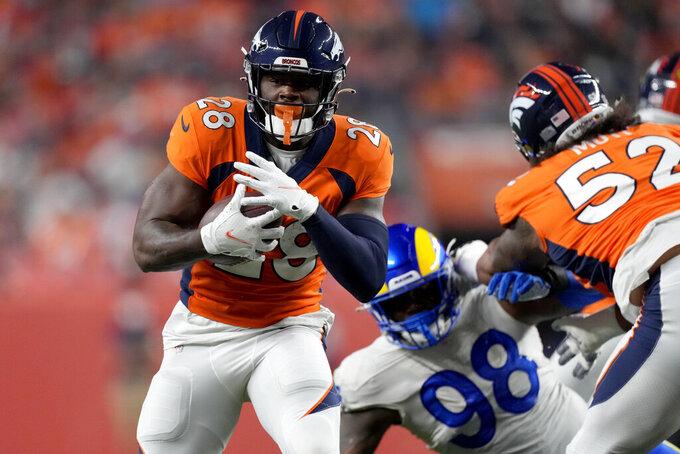 Denver Broncos running back Royce Freeman (28) runs as Los Angeles Rams defensive end Eric Banks (98) defends during the first half of an NFL preseason football game, Saturday, Aug. 28, 2021, in Denver. (AP Photo/David Zalubowski)