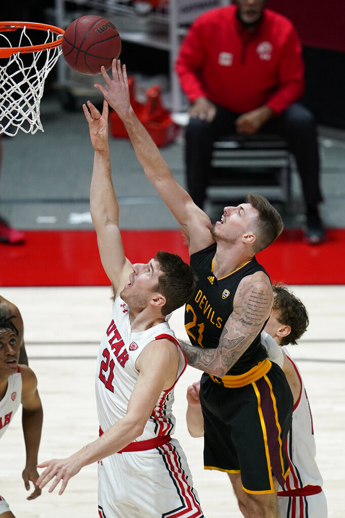 Arizona State forward Chris Osten (21) and Utah forward Riley Battin (21) battle for a rebound in the first half during an NCAA college basketball game Saturday, March 6, 2021, in Salt Lake City. (AP Photo/Rick Bowmer)
