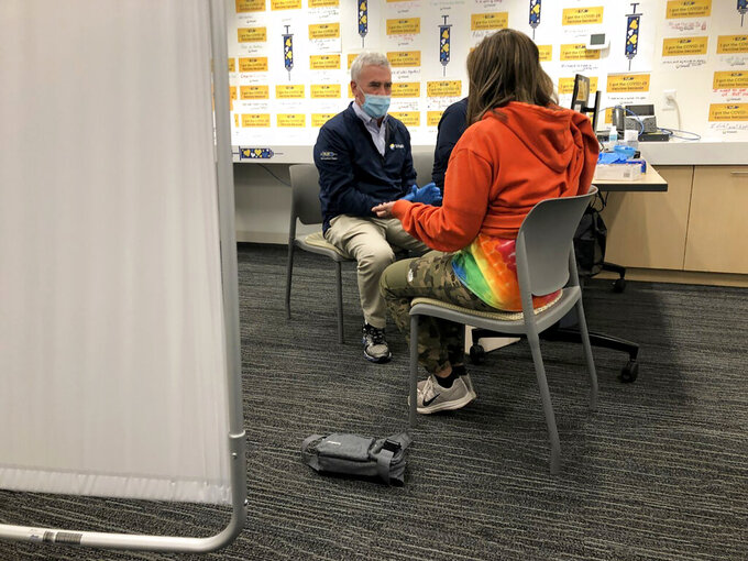 U.S. Rep. Brad Wenstrup, R-Ohio, left, talks with Anu Singh Burns, right, before giving her a COVID-19 vaccine at TriHealth clinic, in Norwood, Ohio on Sunday, March 28, 2021. (AP Photo/Dan Sewell)