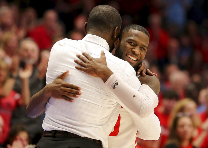 Dayton's Jalen Crutcher, right, hugs head coach Anthony Grant, left, during the second half of an NCAA college basketball game against George Washington, Saturday, March 7, 2020, in Dayton, Ohio. (AP Photo/Tony Tribble)