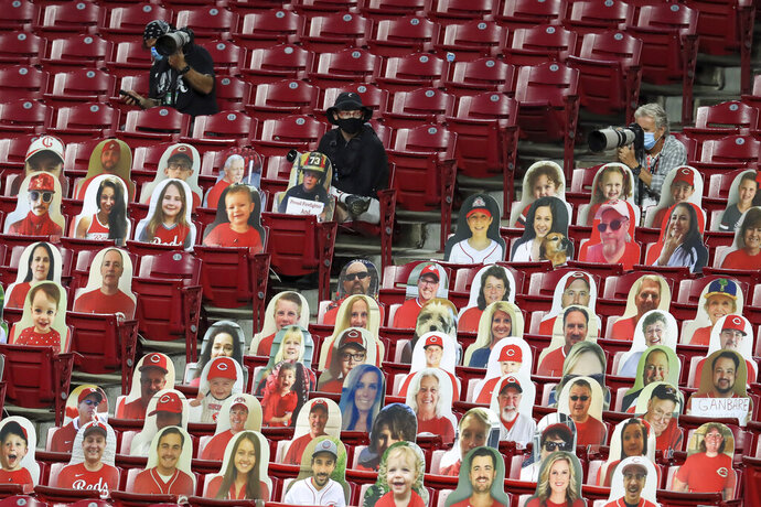 FILE - In this Aug. 3, 2020, file photo, photographers practice social distancing while sitting with fan cutouts during a baseball game between the Cleveland Indians and the Cincinnati Reds in Cincinnati. Ohio Gov. Mike DeWine says pro sports teams could allow up to 30% of fans in stadiums this spring under a pandemic-related plan for sports. (AP Photo/Aaron Doster, File)
