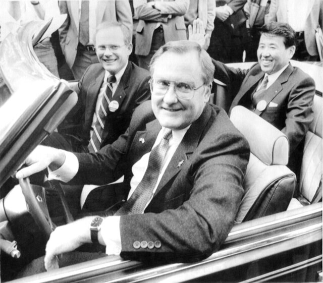 "FILE - In this Oct. 7, 1985 file photo, Illinois Gov. James R. Thompson, behind the wheel of a Chrysler convertible, is joined by G. Glenn Gardner, left, and Yoichi Nakane, after a news conference in Chicago.   Thompson, known as ""Big Jim"" during a long career that eventually made him the state's longest-serving chief executive, has died. He was 84. Thompson died  Friday, Aug. 14, 2020 at the Shirley Ryan AbilityLab in Chicago, his wife, Jayne, told the Chicago Tribune and the Chicago Sun-Times.  (AP Photo/Mark Elias, File)"