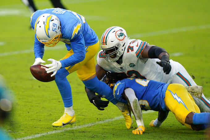 Los Angeles Chargers outside linebacker Nick Vigil (59) recovers a fumble as Miami Dolphins offensive tackle Austin Jackson (73) attempts to tackle, during the first half of an NFL football game, Sunday, Nov. 15, 2020, in Miami Gardens, Fla. (AP Photo/Wilfredo Lee)