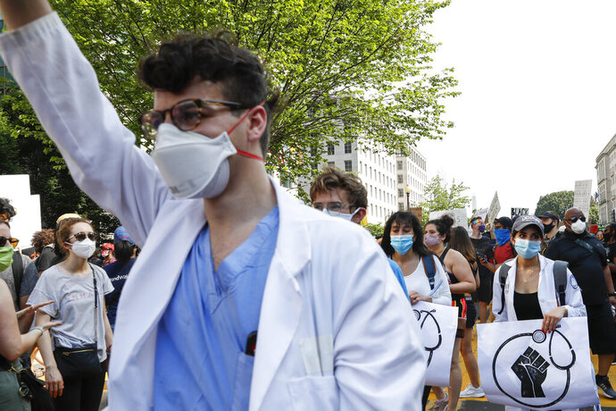 Doctors protest Saturday, June 6, 2020, near the White House in Washington, over the death of George Floyd, a black man who was in police custody in Minneapolis. Floyd died after being restrained by Minneapolis police officers. (AP Photo/Jacquelyn Martin)