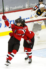 New Jersey Devils center Yegor Sharangovich (17) celebrates with Devils left wing Janne Kuokkanen (59) after scoring a game-tying goal during the third period of an NHL hockey game against the Boston Bruins, Tuesday, May 4, 2021, in Newark, N.J. (AP Photo/Kathy Willens)
