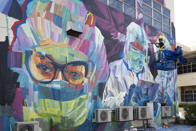 A worker gives final touches to a graffiti that tributes to Malaysian workers on the frontline against the COVID-19 pandemic outside a hospital in Kuala Lumpur, Malaysia, Friday, Jan. 29, 2021. Malaysian authorities imposed tighter restrictions on movement to try to halt the spread of the coronavirus. (AP Photo/Vincent Thian)