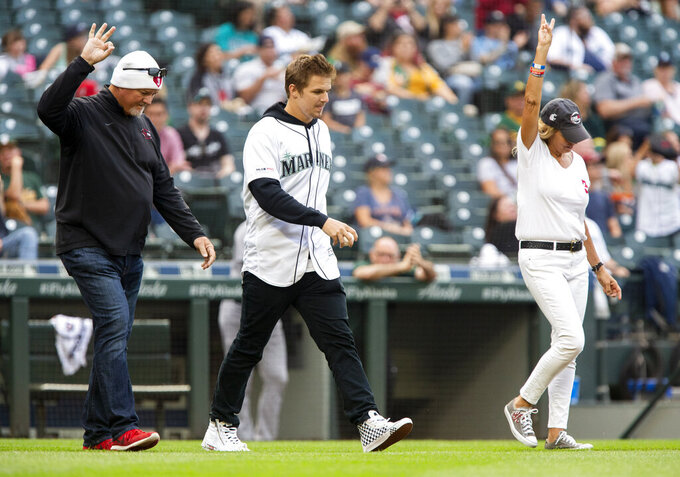 Mark Hilinski, left, Ryan Hilinski and Kym Hilinski, the parents and brother of former Washington State University quarterback Tyler Hilinski, hold up Tyler's No. 3 as they walk out to deliver the ceremonial first pitch before a baseball game between the Seattle Mariners and Oakland Athletics Saturday, July 6, 2019, in Seattle. (AP Photo/Lindsey Wasson)