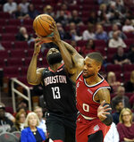 Houston Rockets' James Harden (13) is fouled by Portland Trail Blazers' Damian Lillard (0) during the first half of an NBA basketball game Monday, Nov. 18, 2019, in Houston. (AP Photo/David J. Phillip)
