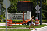 A pedestrian walks past a sign stating that masks, used to prevent the spread of COVID-19, are required to be worn on campus, by an entrance to the University of Miami, Tuesday, Aug. 25, 2020, in Coral Gables, Fla. (AP Photo/Wilfredo Lee)