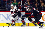 Arizona Coyotes' Ilya Lyubushkin (46), of Russia, works against Carolina Hurricanes' Jordan Martinook (48) and Brock McGinn (23) for the puck during the first period of an NHL hockey game in Raleigh, N.C., Friday, Jan. 10, 2020. (AP Photo/Karl B DeBlaker)