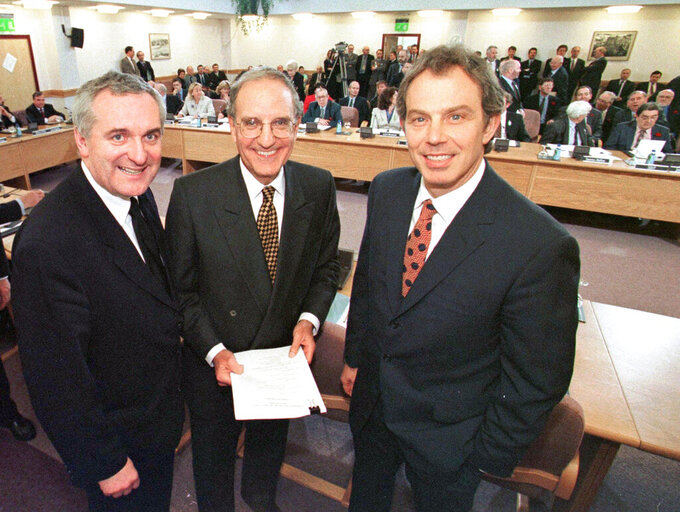 "FILE - In this April 10, 1998, file photo, from right, British Prime Minister Tony Blair, U.S. Sen. George Mitchell, and Irish Prime Minister Bertie Ahern, pose together after they signed the Good Friday Agreement for peace in Northern Ireland. The chaotic scenes during a week of violence on the streets of Northern Ireland have stirred memories of decades of Catholic-Protestant conflict, known as ""The Troubles."" A 1998 peace deal ended large-scale violence but did not resolve Northern Ireland's deep-rooted tensions. (AP Photo/File)"