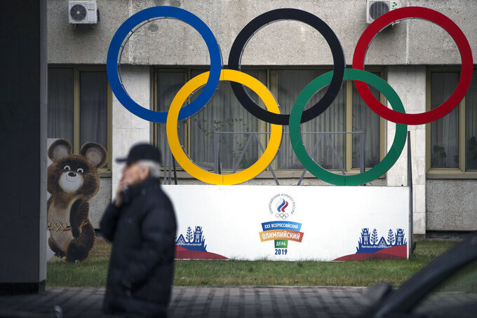 "FILE - In this Nov. 28, 2019 file photo Olympic Rings and a model of Misha the Bear Cub, the mascot of the Moscow 1980 Olympic Games, left, are seen in the yard of Russian Olympic Committee building in Moscow, Russia. In the report detailing its decision to shorten Russia's ban from the Olympics, the highest court in sports blasted that country's leaders for engaging in ""a cover up of the cover-up"" in a desperate attempt to deny their culpability, but reduced the punishment nonetheless, Wednesday, Jan. 13, 2021. (AP Photo/Pavel Golovkin, file)"