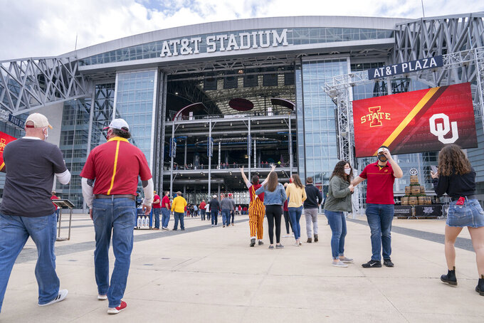Fans enter AT&T Stadium before an NCAA college football game between Iowa State and Oklahoma for the Big 12 Conference championship, Saturday, Dec. 19, 2020, in Arlington, Texas. (AP Photo/Jeffrey McWhorter)