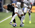 Sporting Kansas City midfielder Roger Espinoza, left, tangles with Minnesota United defender Romain Metanire (19) during the first half of an MLS soccer match in Kansas City, Kan., Thursday, Aug. 22, 2019. (AP Photo/Orlin Wagner)