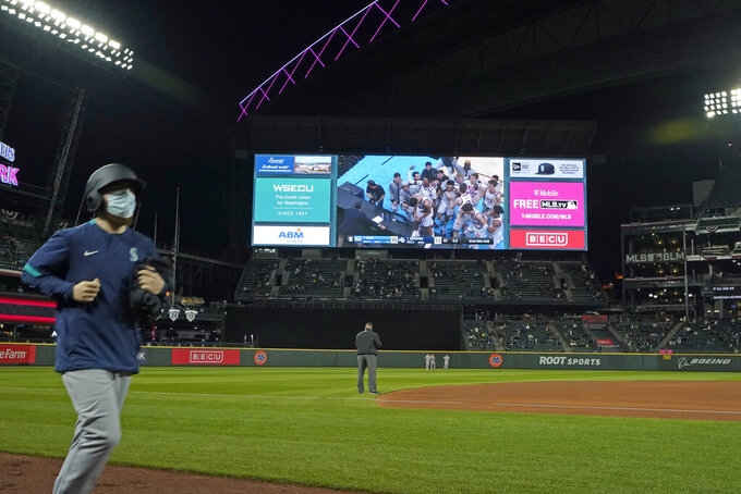 Celebrating Gonzaga players are shown on a video screen at T-Mobile Park on Saturday, April 3, 2021, in Seattle between innings of a baseball game between the Seattle Mariners and the San Francisco Giants after Gonzaga defeated UCLA in overtime in an NCAA college basketball Final Four game. (AP Photo/Ted S. Warren)