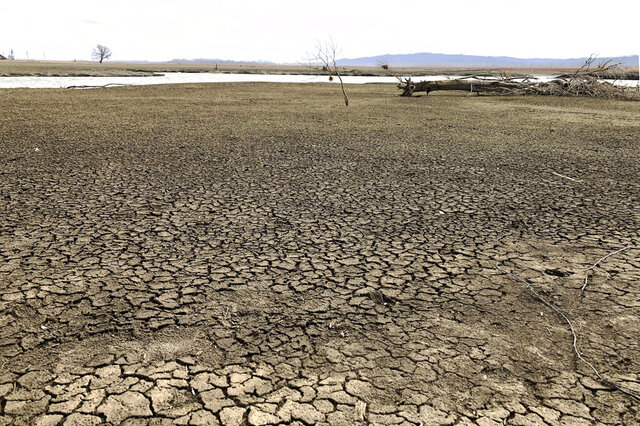This photo taken March 12, 2020, near Rock Port, Missouri, shows once-productive farmland that was ruined after a Missouri River flood blew open part of an earthen levee and inundated the area in 2019. The landowner is among several in the area who have offered to sell about 500 acres so the levee can be moved farther back, giving the river more room to roam. Levee setbacks are among measures being taken in the U.S. heartland to control floods in ways that work with nature instead of trying to dominate it with concrete infrastructure. (AP Photo/John Flesher)