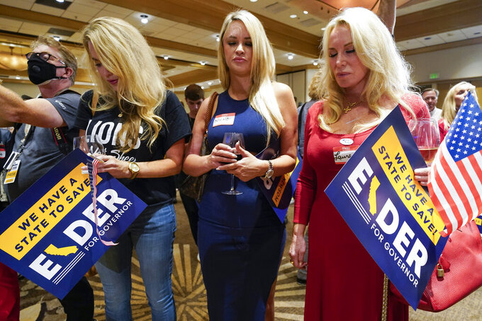 Supporters of Republican conservative radio show host Larry Elder pray as polls close for the California gubernatorial recall election Tuesday, Sept. 14, 2021, in Costa Mesa, Calif. The rare, late-summer election, which challenged California Gov. Gavin Newsom, has emerged as a national battlefront on issues from COVID-19 restrictions to climate change. (AP Photo/Ashley Landis)