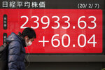 A man walks past an electronic stock board showing Japan's Nikkei 225 index at a securities firm in Tokyo, Friday, Feb. 7, 2020. Asian stock markets have retreated following a surge driven by a Chinese tariff cut on U.S. imports. (AP Photo/Eugene Hoshiko)