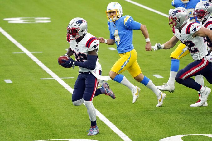 New England Patriots' Devin McCourty, left, returns a blocked field goal for a touchdown during the first half of an NFL football game against the Los Angeles Chargers Sunday, Dec. 6, 2020, in Inglewood, Calif. (AP Photo/Ashley Landis)