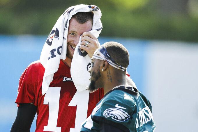 Philadelphia Eagles quarterback Carson Wentz, left,  and wide receiver DeSean Jackson meet during practice at the NFL football team's training camp in Philadelphia, Friday, July 26, 2019. (AP Photo/Matt Rourke)