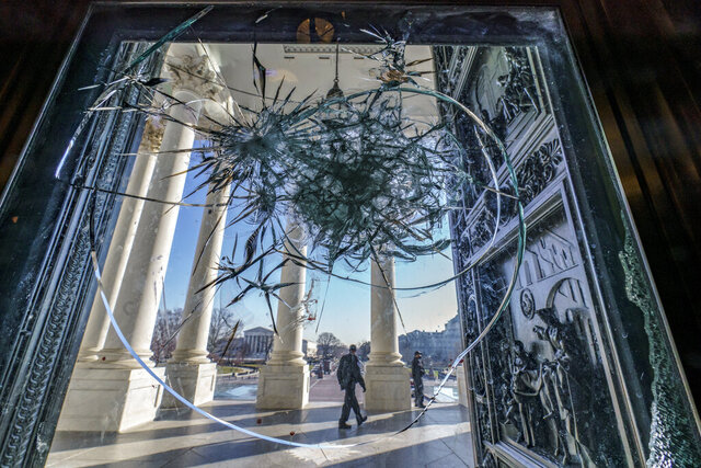 Shattered glass from the previous week's attack on Congress by a pro-Trump mob is seen in doors leading to the Capitol Rotunda in Washington on Tuesday, Jan. 12, 2021. (AP Photo/J. Scott Applewhite)