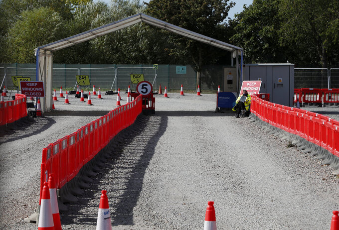 Staff waits beside the empty lanes of a Covid-19 drive thru testing facility at Twickenham stadium in London, Thursday, Sept. 17, 2020. Britain has imposed tougher restrictions on people and businesses in parts of northeastern England on Thursday as the nation attempts to stem the spread of COVID-19, although some testing facilities remain under-utilised. (AP Photo/Frank Augstein)