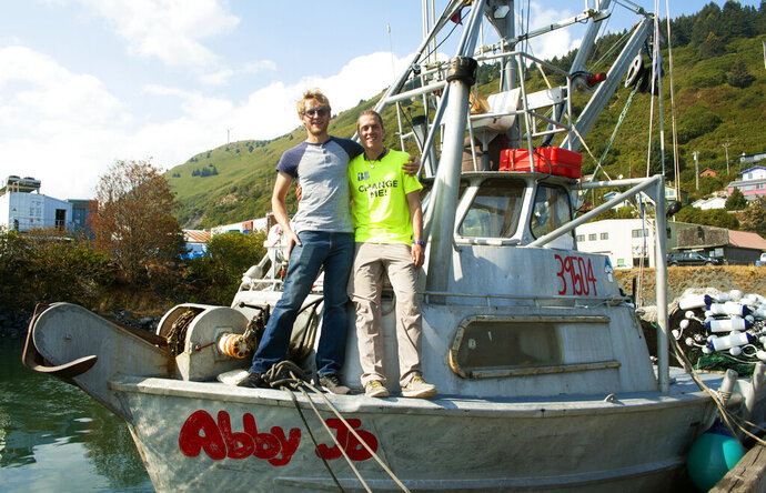 In this Aug. 28, 2019 photo, Jake Organ, left, captain of the Abby Jo, poses with filmmaker Yonatan Belik on the bow of the boat at the harbor in Kodiak, Alaska, The local seining industry is the star of a short video produced by Belik, an Israeli filmmaker and traveler who spent the summer working as a skiffman in Kodiak. The video, titled
