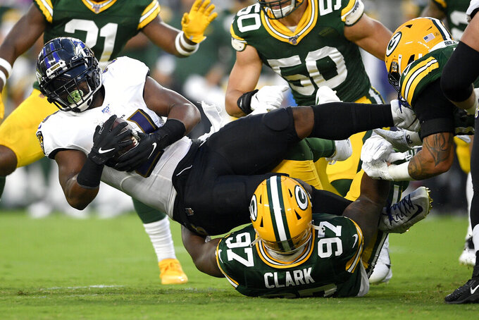 Baltimore Ravens running back Mark Ingram, left, is tackled by Green Bay Packers nose tackle Kenny Clark (97) during the first half of a NFL football preseason game, Thursday, Aug. 15, 2019, in Baltimore. (AP Photo/Nick Wass)
