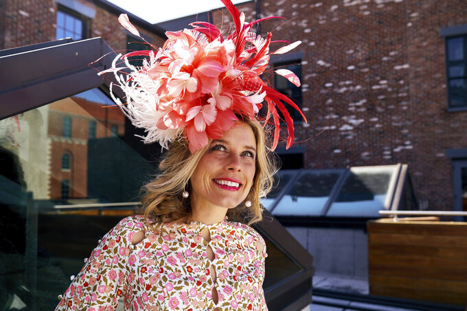 """FILE - In this undated photo provided by Jessa Mayhew in April 2020, hat maker Kenzie Kapp models one of her fascinator designs for the Kentucky Derby in Louisville, Ky. The Kentucky Derby is back on the first Saturday in May 2021, slowly bringing with it the sights, sounds and rituals familiar to Louisville. And local officials and business owners are hopeful it translates into better cash flow after the coronavirus pandemic upended the Derby's schedule the previous year. """"It definitely smells like Derby,"""" said business owner and Louisville native Kapp, who's relishing a boost in demand making masks to match her hats and fascinators. (Jessa Mayhew via AP)"""