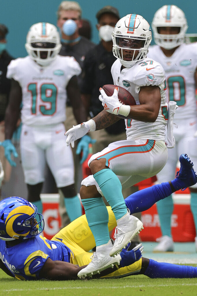 Miami Dolphins running back Myles Gaskin (37) catches a pass over the defense of Los Angeles Rams defensive back Darious Williams (31) in an NFL game, Sunday, Nov. 1, 2020 in Miami Gardens, Fla. The Dolphins defeated the Rams 28-17. (Margaret Bowles via AP)