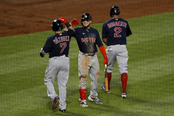 Boston Red Sox's Alex Verdugo, center, celebrates with Christian Vazquez, left, and Xander Bogaerts after Bogaerts hit a two-run homer run during the fourth inning of the baseball game against the New York Mets at Citi Field, Thursday, July 30, 2020, in New York. (AP Photo/Seth Wenig)
